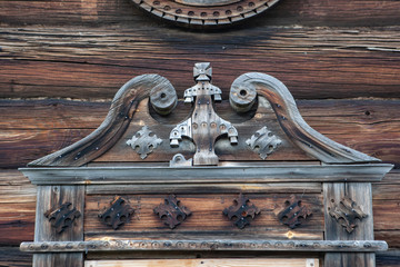 Decorative element of the window on the facade in an old traditional wooden house