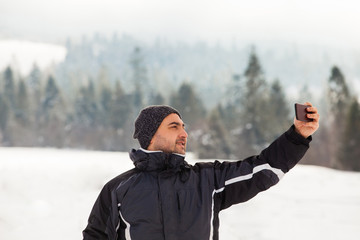 Photo on winter walk, man does selfie