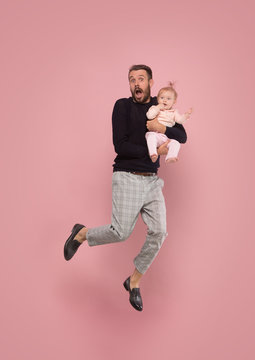 The studio shot of surprised dad with little girl jumping on pink studio background. Freedom in moving