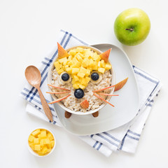 Healthy breakfast oatmeal porridge for kids. Funny creative food art for kids. Cute fox made with fruits and berries on oatmeal porridge. Top view
