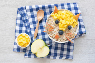 Funny Breakfast For Kids. Oatmeal Porridge With Cute Fruit Face. Porridge with fruits and berries for healthy breakfast