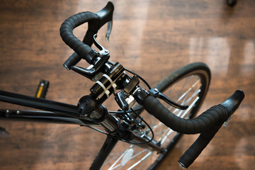 Road bike or racing type bicycle, on a wooden floor of a cycle workshop. Focus on handle , shallow depth of field.