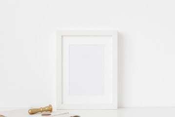 White a5 portrait frame mockup with gold stamp and printing on white wall background. Empty frame, poster mock up for presentation design.
