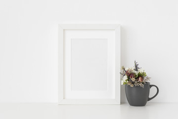 Elegant white A5 portrait frame mockup with small bouquet of dried flowers in a mug on white wall background. Empty frame, poster mock up for presentation design.