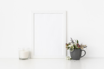 White a4 portrait frame mockup with dried field wild flowers in vase and white candle on white wall background. Empty frame, poster mock up for presentation design.