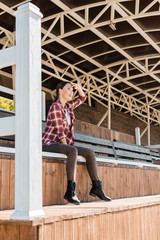 attractive cowgirl in checkered shirt sitting on bench at ranch stadium and looking at something
