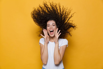 Photo of caucasian woman 20s laughing and having fun with shaking hair, isolated over yellow background
