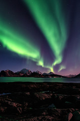 Night winter landscape with Northern lights, Aurora borealis. Scenery view of the Lofoten Islands, Norway. Vertical image