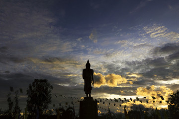 Statue of Buddha standing in the park and dramatic evening sky.