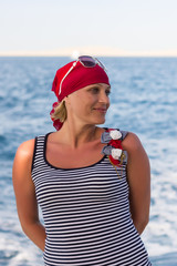 Portrait of a suntanned slender girl in a red bandana against the blue sea