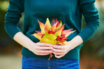Young woman with bunch of colorful autumn leaves