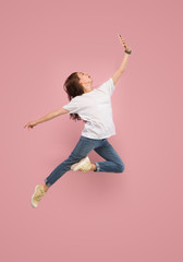 Always on mobile. Full length of pretty young woman taking phone and making selfie while jumping against pink studio background. Mobile, motion, movement, business concepts