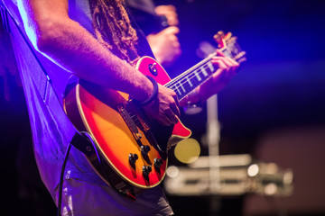 Guitarist playing on electric bass guitar on stage. Colorful, soft focus and blur background