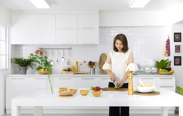 Beautiful Asian woman showing her new kitchen decoration and play with fake fruits and vegetables. Concept to modern housewife work.