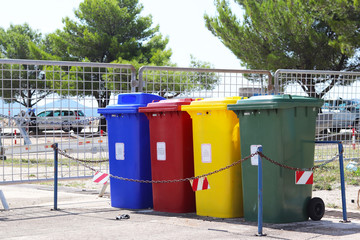 Four multicolored boxes for sorted garbage: red, green, blue and yellow. Recycling garbage in the tourist area. Infrastructure of the Mediterranean marina. Plastic waste containers.