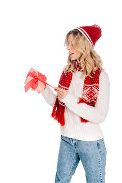 surprised young woman in scarf and hat opening gift box isolated on white