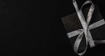 Black gift box with silver ribbon bow on black background. Top view, copy space