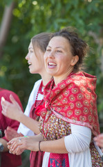 Smiling young women in russian folk costumes on the tree background
