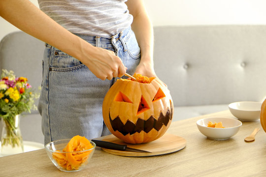 Close up of young woman carving Jack O Lattern from ripe orange pumpkin with knife on her wooden kitchen table. Female preparing all hallows eve Halloween party decorations. Background, copy space.