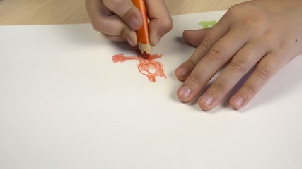 A picture of a child on paper. The view from above, the child draws in colored pencils.