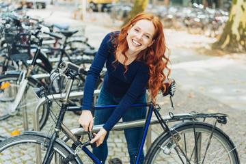 fröhliche studentin schließt ihr fahrrad ab