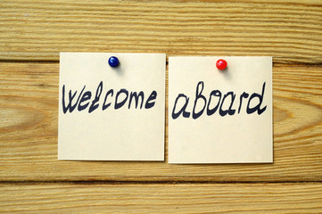 Welcome aboard written on Sticky notes and posted on wooden background