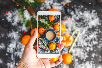 Christmas and New Year's concept. Female hands photographed on a smartphone a New Year's composition of mandarin, spruce branches, snow and a cup of coffee