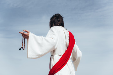 back view of Jesus in robe, red sash and crown of thorns holding rosary against blue sky