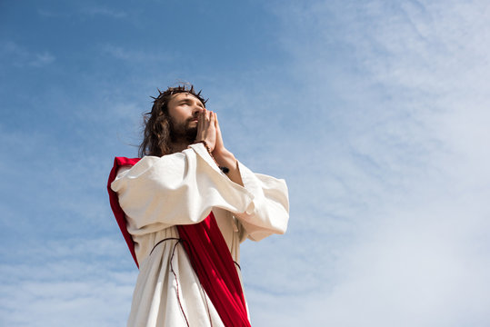 low angle view of Jesus praying against blue sky