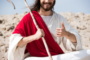 cropped image of Jesus sitting in lotus position on sand, holding staff and showing thumb up in desert