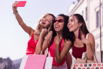 Our photo. Joyful happy woman holding her smartphone while taking a selfie together with friends