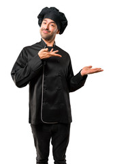 Chef man In black uniform extending hands to the side and smiling for presenting and inviting to come on isolated white background