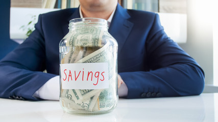 Concept of successful money saving. Young businessman with glass jar for savings full of money