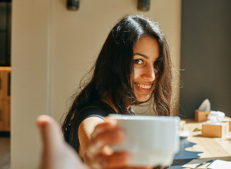 a happy young woman, offers you coffee