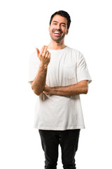 Young man with white shirt presenting and inviting to come with hand. Happy that you came on isolated white background
