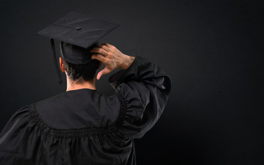 Man on his graduation day University on back position looking back while scratching head on black background