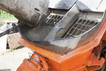 close up view of the flowing concrete from concrete mixer machine to the pump