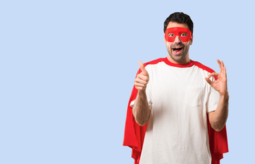 Superhero man with mask and red cape showing an ok sign with fingers and giving a thumb up gesture with the other hand on isolated blue background