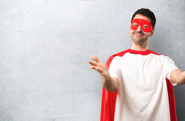 Superhero man with mask and red cape presenting and inviting to come with hand. Happy that you came on textured grey background