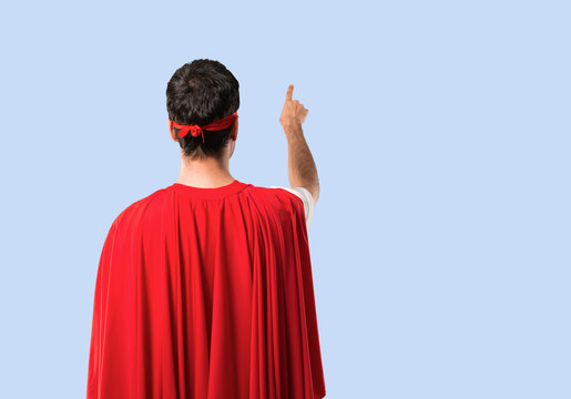 Superhero man with mask and red cape pointing back with the index finger on isolated blue background