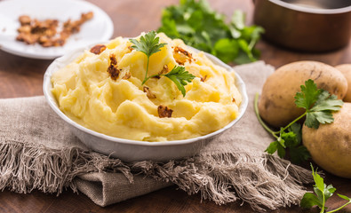 Mashed potatoes in bowl decorated with parsley herbs.