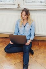 frau sitzt vor der heizung auf dem boden und schaut auf ihren laptop