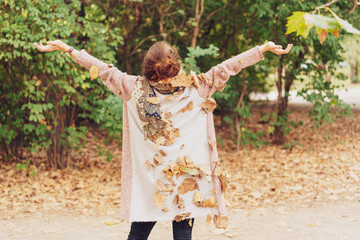 woman raising her arms embracing autumn forrest