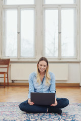 lächelnde frau sitzt in der leeren wohnung mit laptop auf dem boden