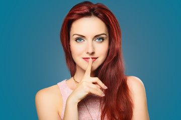 Beautiful woman with red hairs, finger on lips. Secret.
