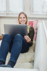 lächelnde junge frau liegt mit ihrem laptop auf dem sofa