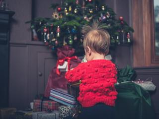 Cute little boy opening christmas presents