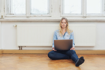 junge frau sitzt auf dem boden vor der heizung und schaut auf ihren laptop