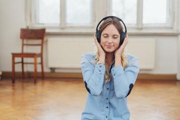 frau hört musik mit geschlossenen augen in einer leeren wohnung