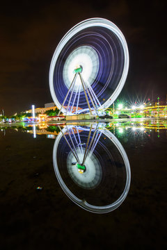 Ferris wheel at amusement park with reflections on the water